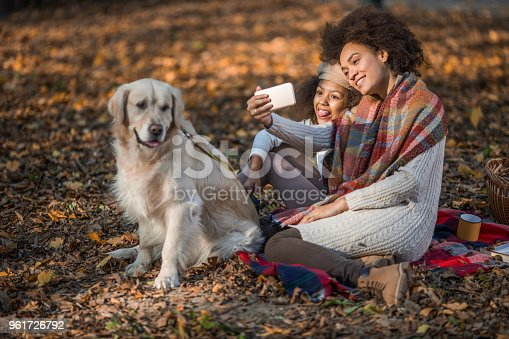 istock Playful African American mother and daughter having fun while taking a selfie with mobile phone. 961726792