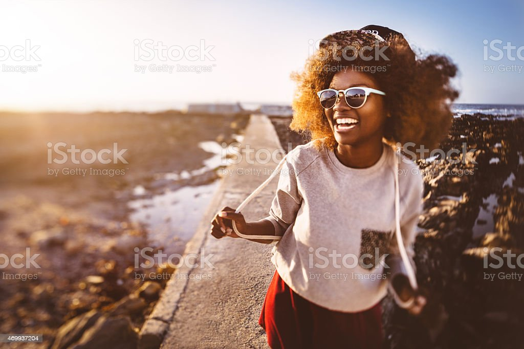 Playful African American teen hipster at the beach stock photo