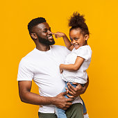 Beep. Playful african girl playing with daddy, pushing his nose like signal, orange background