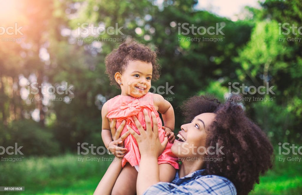 Playful African-American mom and daughter in the park stock photo
