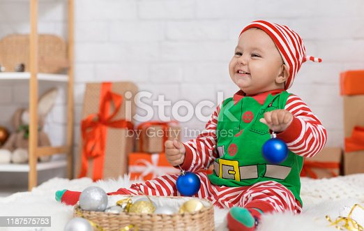 Cute Christmas card. Adorable baby playing with decorations under Xmas tree