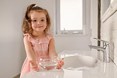 Front view of sweet baby girl wearing pink dress feeling happy and cleaning in the bathroom looking at the camera