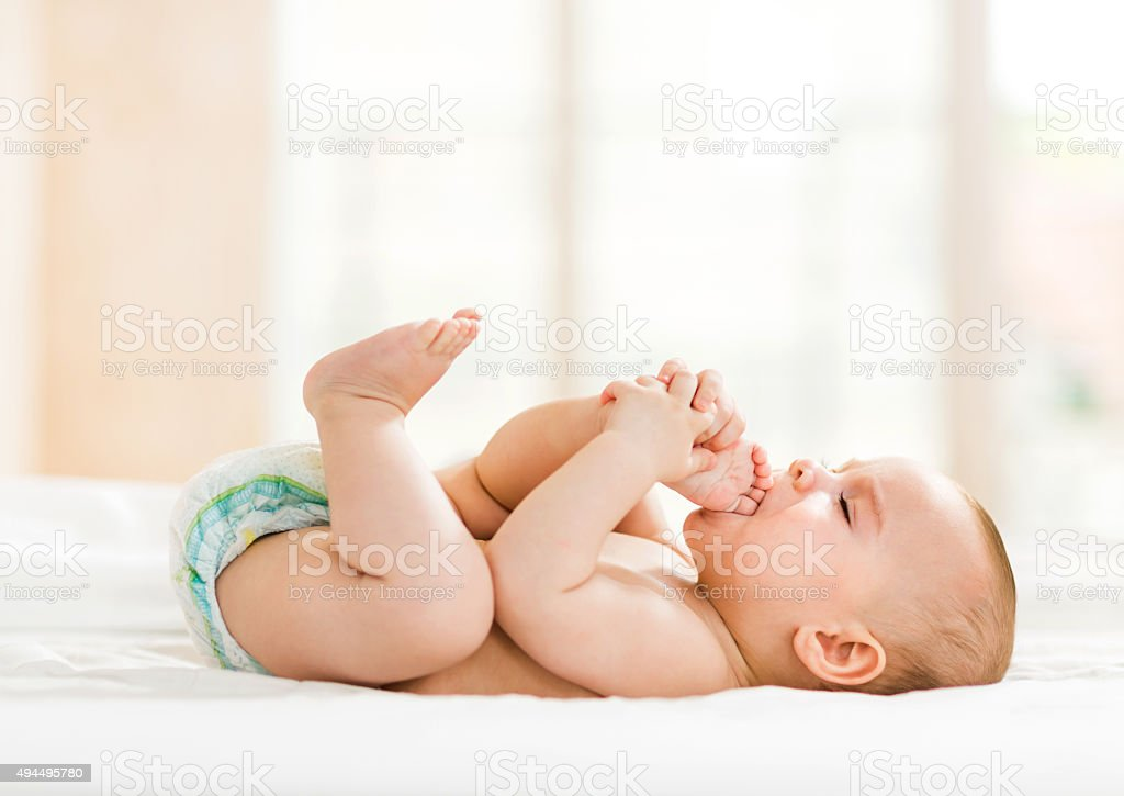 Playful baby lying down in bed. stock photo