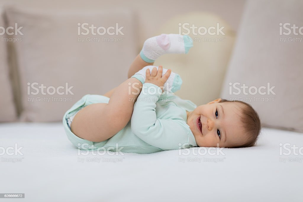 Playful baby lying down in bed stock photo