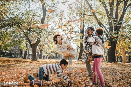Happy African American family having fun while throwing autumn leaves in the park.