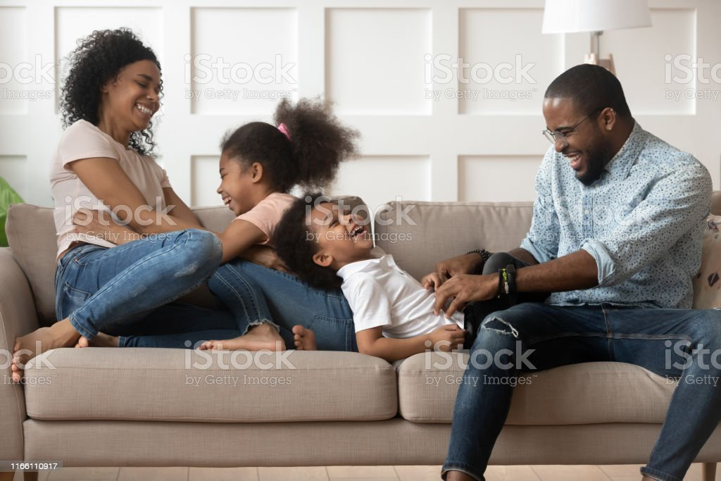 Happy black young parents relax on couch with preschooler kids...