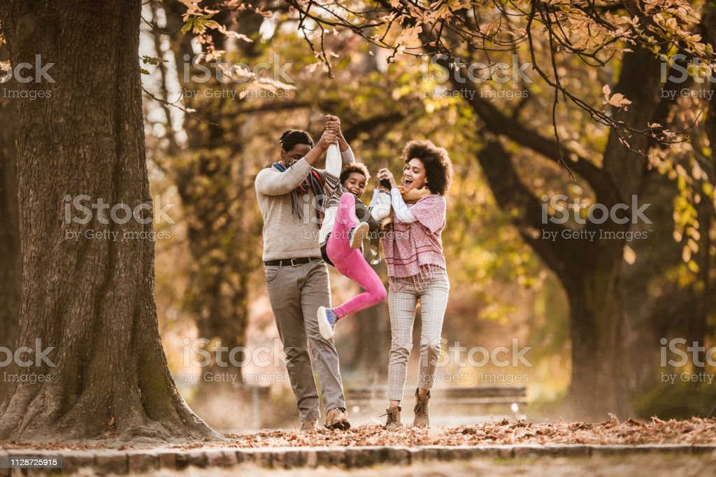 Happy African American parents holding hands with their small...