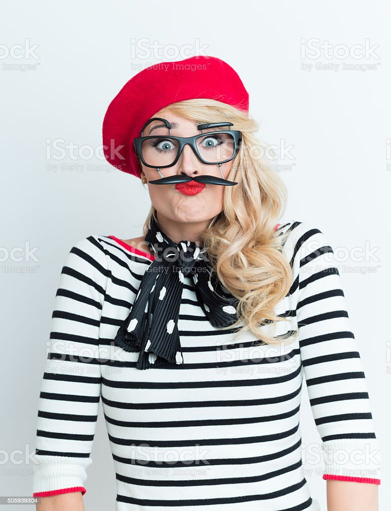 Playful blonde french woman wearing red beret and facial mask Portrait of playful blonde woman in french outfit, wearing a red beret, striped blouse, neckerchief and funny facial mask, staring at camera. Adult Stock Photo
