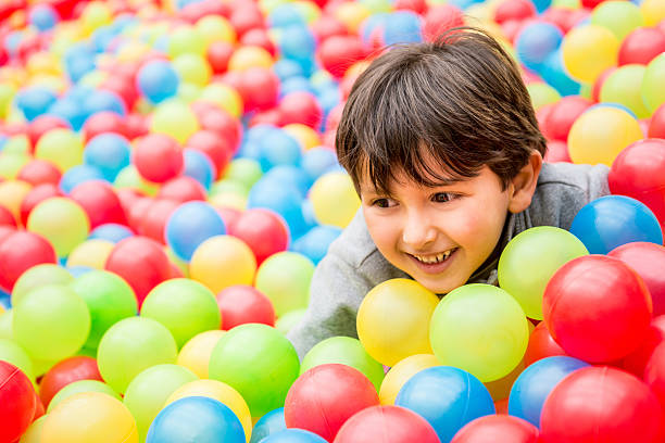 Playful boy at the ball pool stock photo