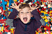 A little happy blond boy with blond hair and blue eyes lies between a lot of colorful plastic blocks toy / building blocks.