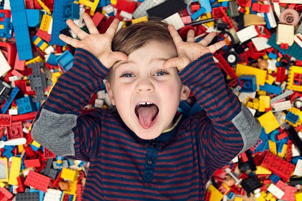 playful boy between plastic blocks A little happy blond boy with blond hair and blue eyes lies between a lot of colorful plastic blocks toy / building blocks. protruding stock pictures, royalty-free photos & images