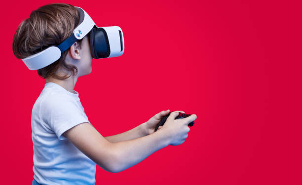 playful boy in vr goggles and with gamepad - vr red background imagens e fotografias de stock