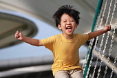 Portrait of playful east asian boy jumping for joy in a modern park