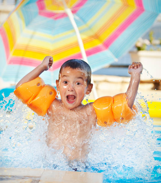 playful boy splashing in the swimming pool - swim arms imagens e fotografias de stock