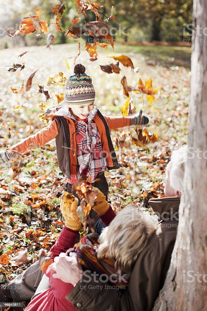 Divertido niño tirando hojas de otoño a los abuelos foto de stock libre de derechos