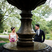 Playful bride and groom standing behind fountain