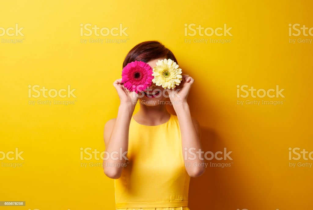 Playful brunette covering her eyes stock photo