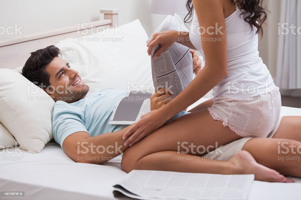 Playful brunette straddling her boyfriend reading paper stock photo
