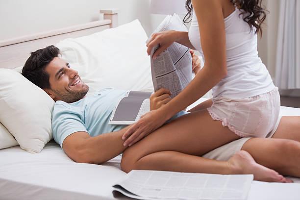 juguetón brunette straddling su novio libro de lectura - piernas abiertas mujer fotografías e imágenes de stock