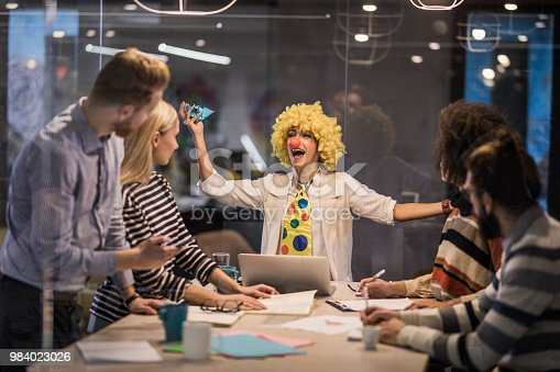 Young businesswoman having fun while pretending to be a clown on a meeting in the office. The view is through glass.
