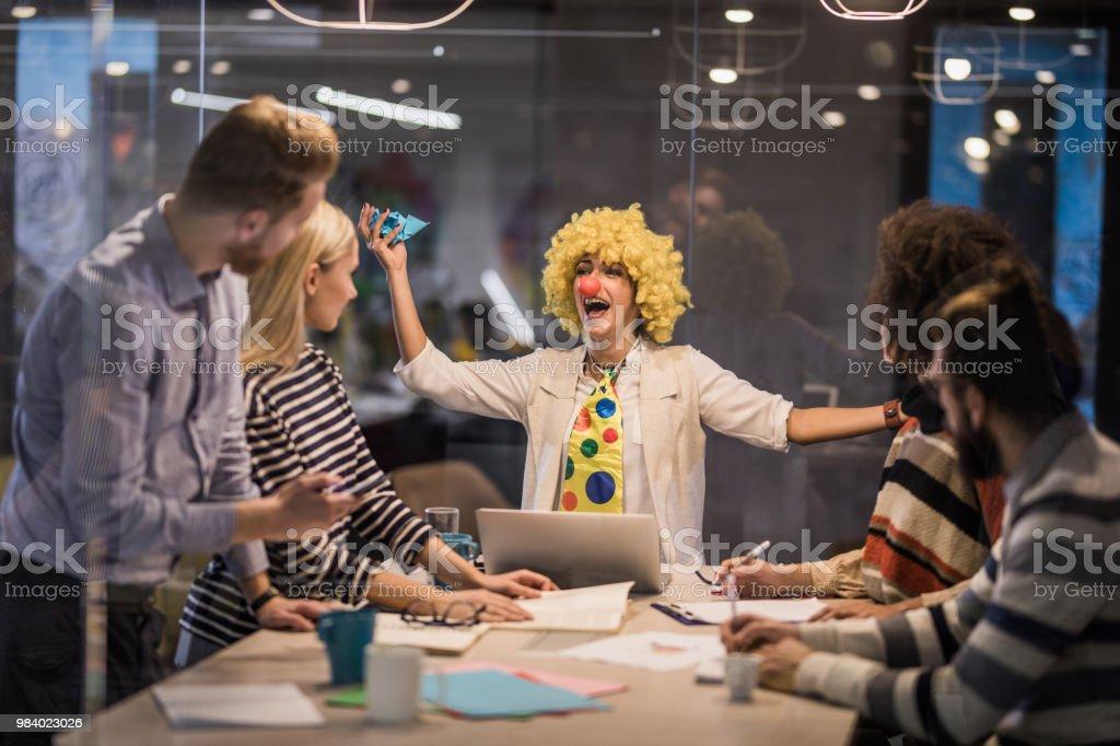 Empresária lúdica, fazendo um palhaço de si mesma em uma reunião no escritório. - foto de acervo