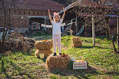 Cheerful and playful child playing outdoors on a farm during Easter.