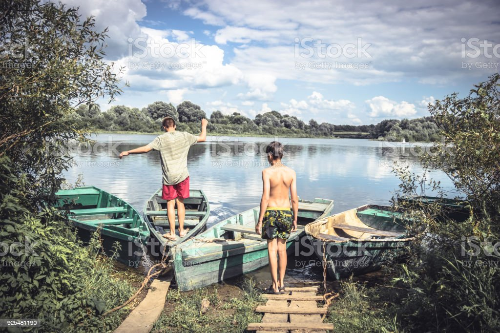 Playful children friends playing countryside summer river during countryside summer holidays stock photo