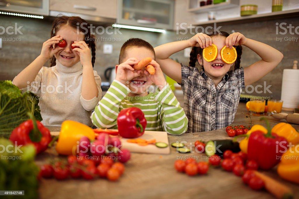 Playful children having fun in the kitchen. stock photo
