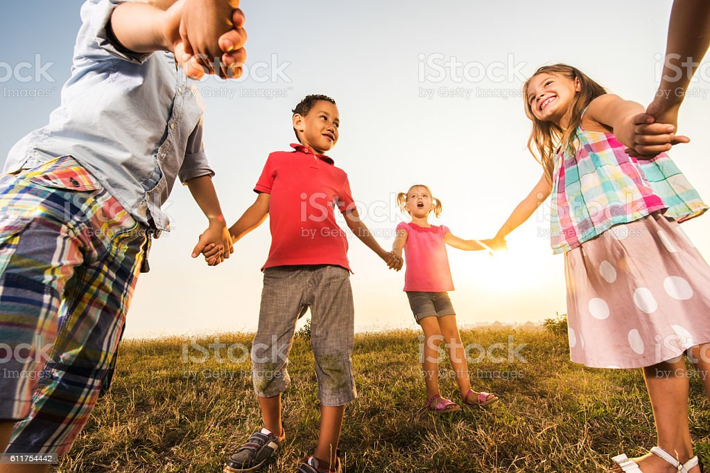 Playful children holding hands in a meadow at sunset. - Photo