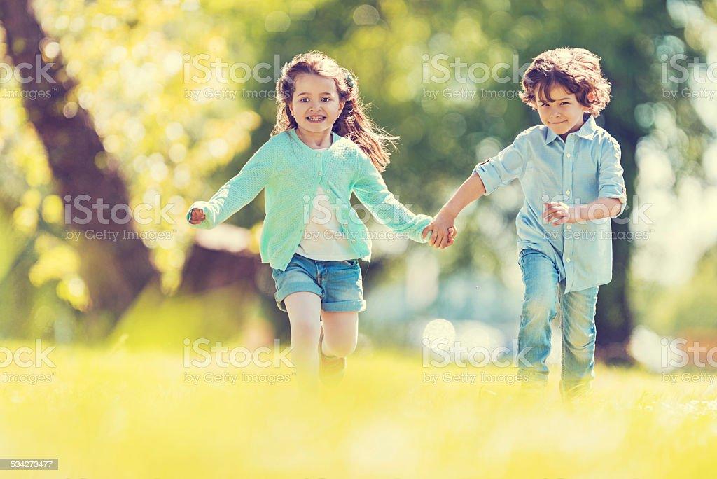 Playful children running outdoors. stock photo