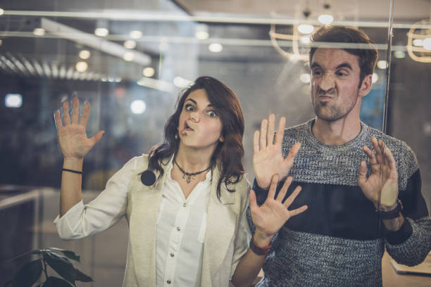 Playful colleagues having fun while sticking their faces on glass wall. stock photo