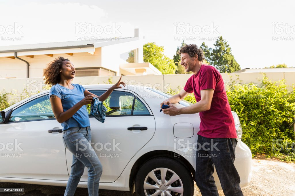 Playful couple cleaning car at yard stock photo