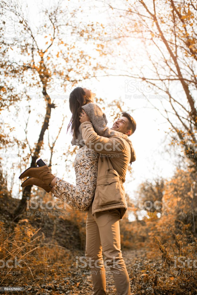 Playful couple having fun during autumn day in the forest. stock photo