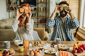 Young happy couple covering their eyes with fresh fruit and having fun at dining table.