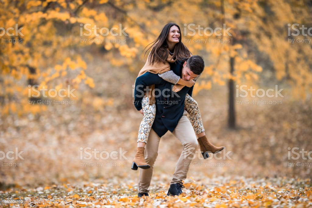 Playful couple having fun while piggybacking during autumn day in the forest. stock photo