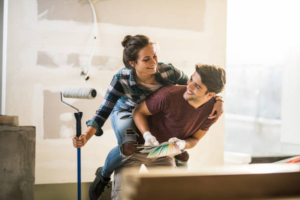 Playful couple having fun while piggybacking during home renovation process. stock photo
