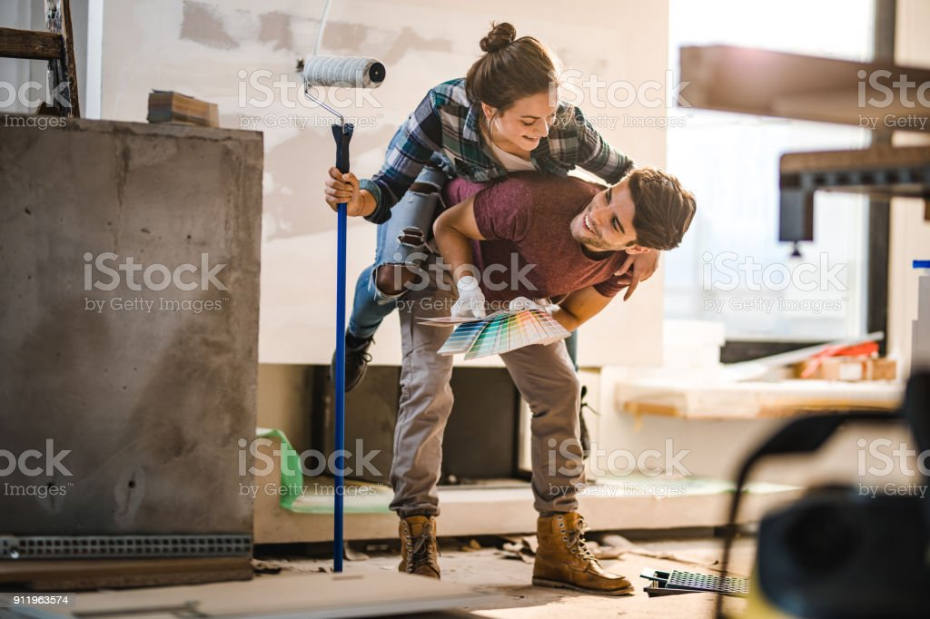Playful couple having fun while piggybacking during home renovation process. stock photo