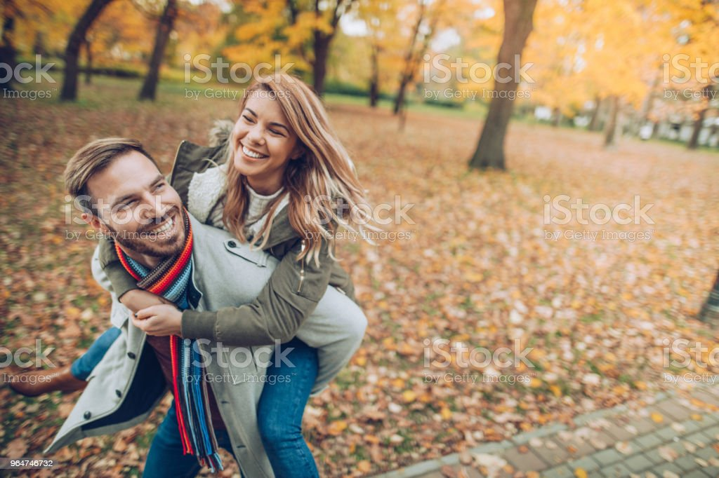 Playful couple having fun while piggybacking in autumn at the park. royalty-free stock photo