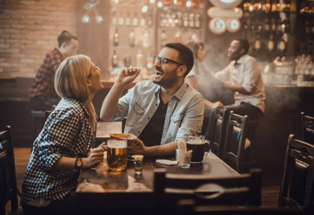 playful couple having fun with peanut during their night out in a pub. - peanut food stock photos and pictures