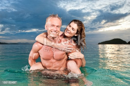 A fit man standing waist deep in the ocean at sunset and carrying a beautiful woman piggyback. They are both laughing as he spins her around playfully. They are affectionate and enjoying being together on this tropical island vacation.