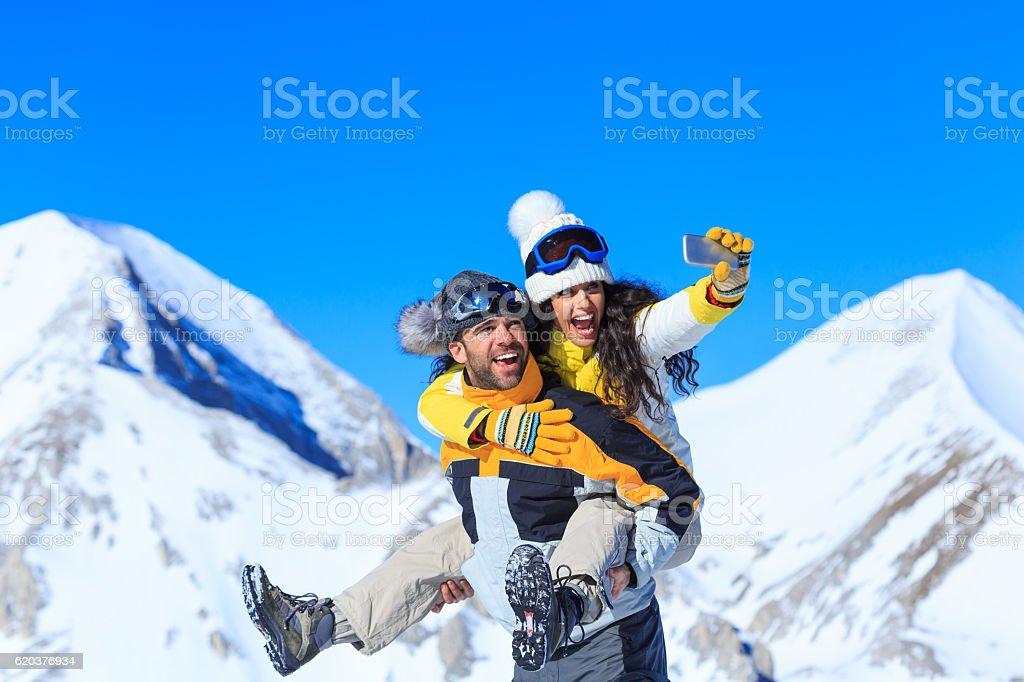 Playful couple making selfie on top snow mountain zbiór zdjęć royalty-free
