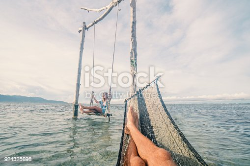 910783248 istock photo Playful couple on the sea, girl on swing, man on hammock 924325698
