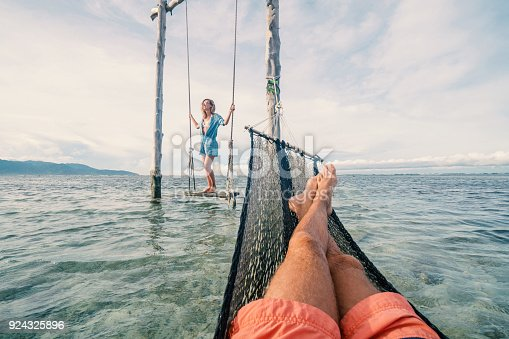 910783248 istock photo Playful couple on the sea, girl on swing, man on hammock 924325896