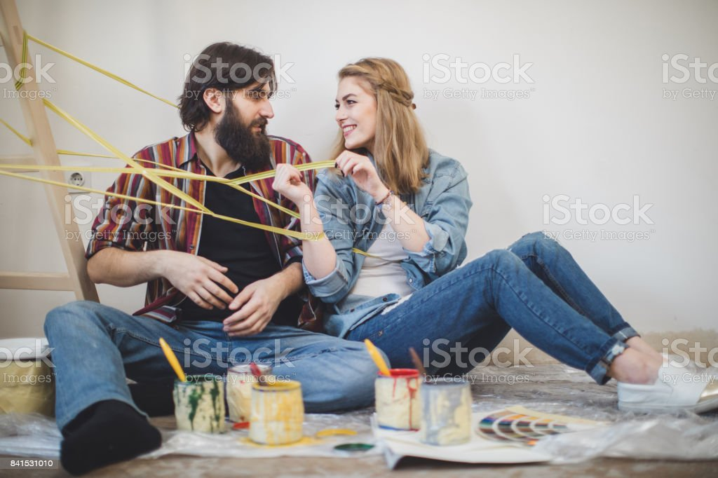 Playful couple preparing to paint walls stock photo