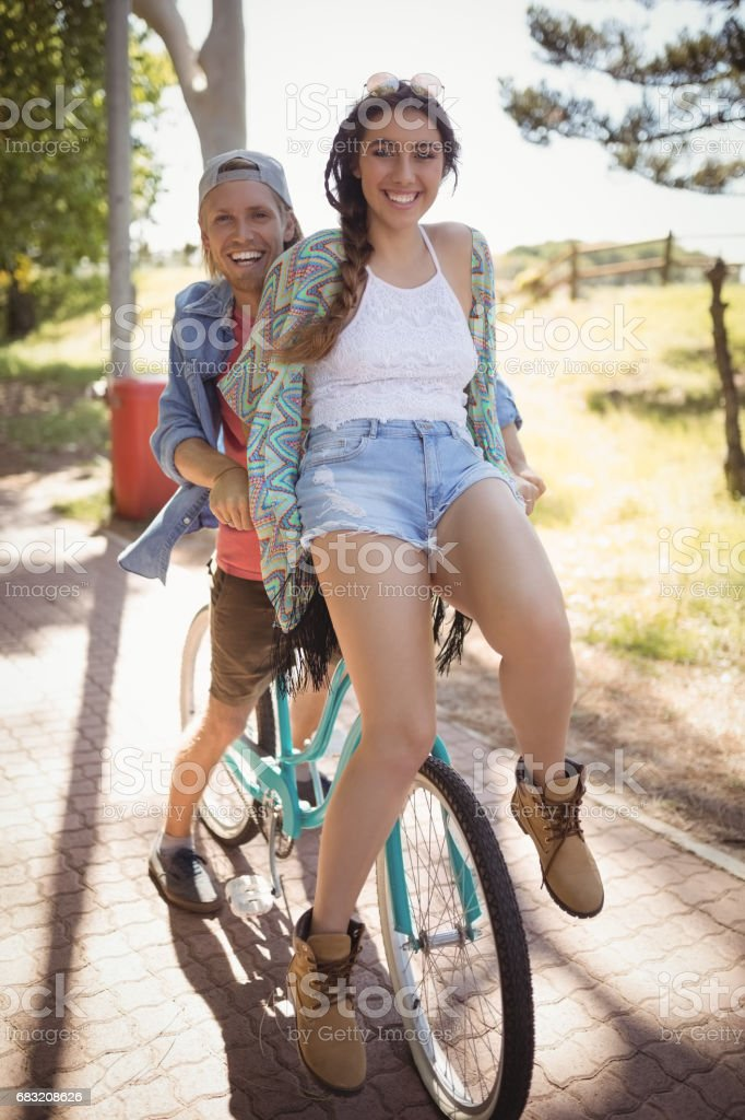 Playful couple sitting on bicycle at footpath foto de stock royalty-free