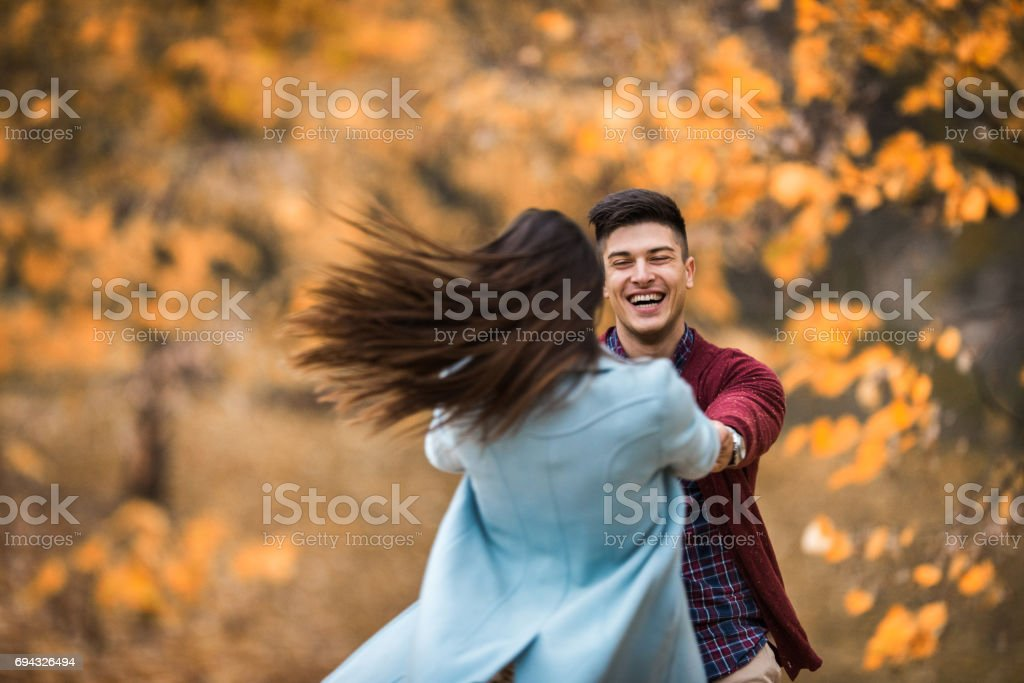 Playful couple spinning and having fun in autumn day at the park. stock photo