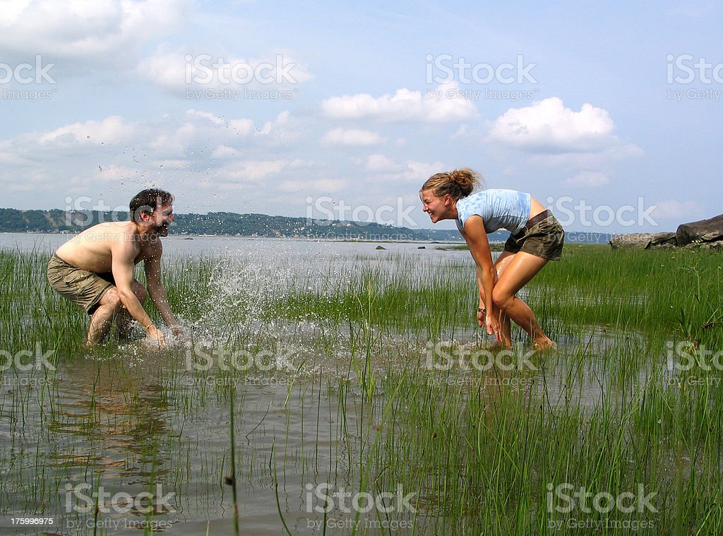 Playful couple splashing water royalty-free stock photo
