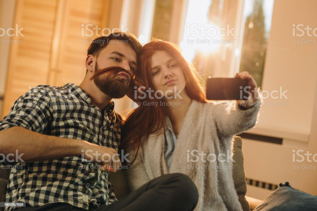 Playful couple taking a selfie with cell phone in the living room. zbiór zdjęć royalty-free