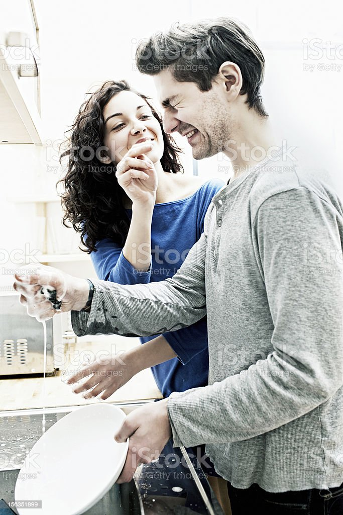 Playful couple washing dishes at home. royalty-free stock photo