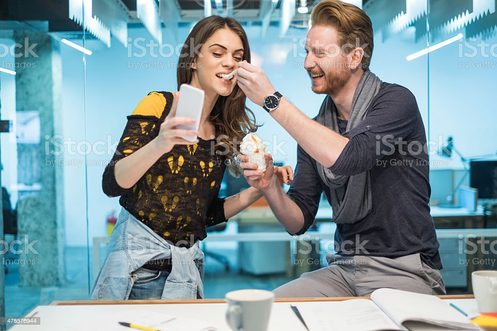 Playful creative couple taking a selfie on a break. Young couple having fun in the office on a break. Man is feeding his girlfriend with ice-cream while she is taking a selfie with mobile phone. 2015 Stock Photo